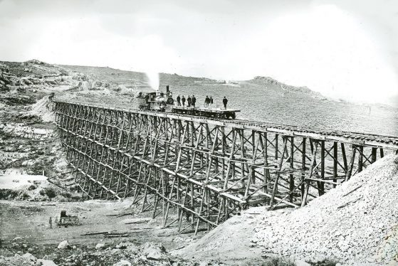 Black and white photo of a wooden train track bridge